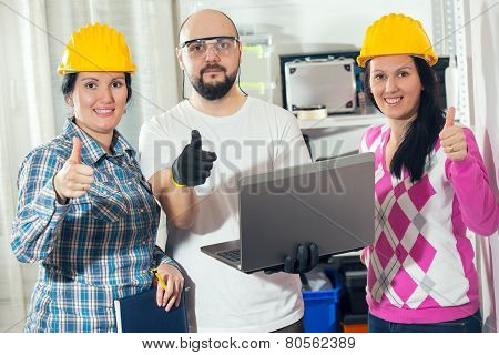 Craftsman and two craftswoman showing thumbs up, selective focus