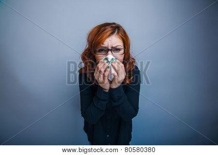 European-looking woman of 30 years is sick, sneezing, handkerchi
