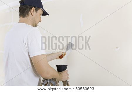 Man Spackles Cracks In Wall