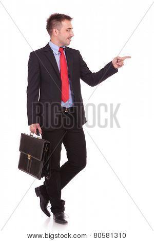 Attractive young business man pointing at something to his left while holding a black briefcase. poster