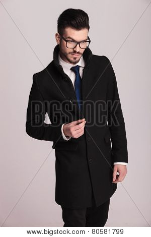 Young elegant business man snapping his fingers while looking down, on grey studio background.