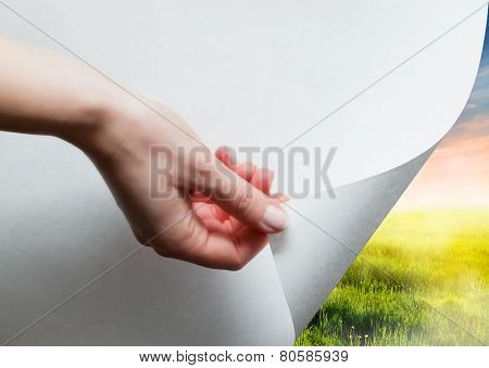 Hand pulling a bottom paper corner to uncover, reveal green landscape. Page curl, conceptual.