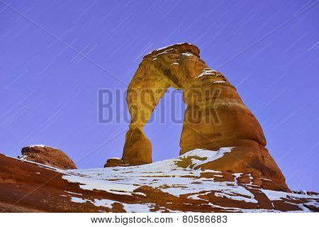 Startrails and Delicate Arch in Arches National Park Utah in winter poster