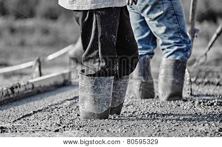 Concrete Workers In Heavy Boots Working In New Wet Concrete.