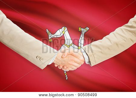 Businessmen shaking hands with flag on background - Isle of Man poster