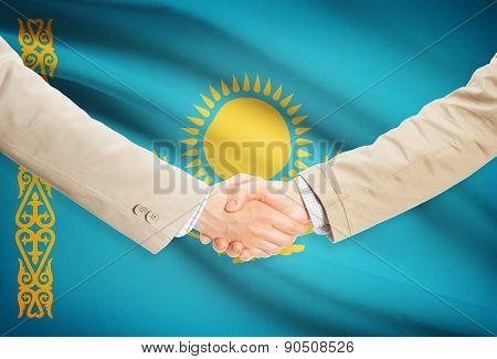 Businessmen Handshake With Flag On Background - Kazakhstan