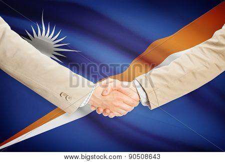 Businessmen Handshake With Flag On Background - Marshall Islands