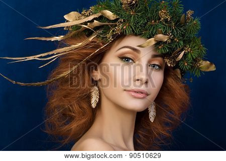 Portrait of young beautiful redhaired woman with firry wreath