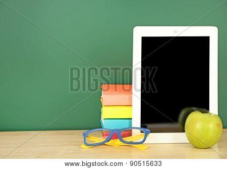 Tablet on table, on green blackboard background