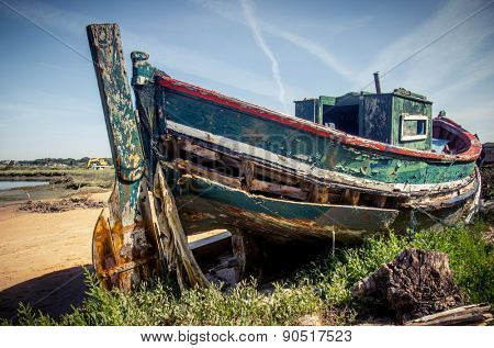 The remains of an old fishing boat rotting on the river shore