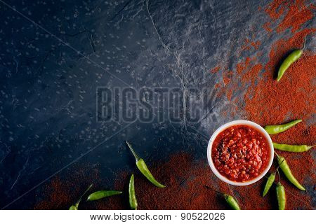 Chilli and garlic relish on black slate background from above