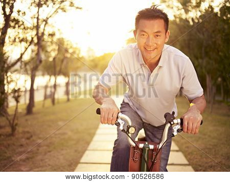 Asian Man Riding Bike Outdoors At Sunset
