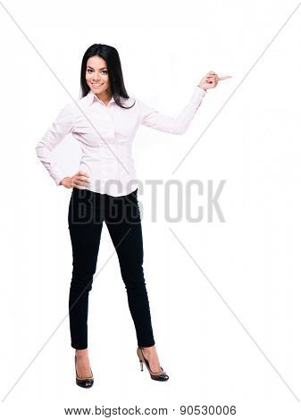 Full length portrait of a cheerful businesswoman pointing finger away. Isolated on a white background. Looking at camera