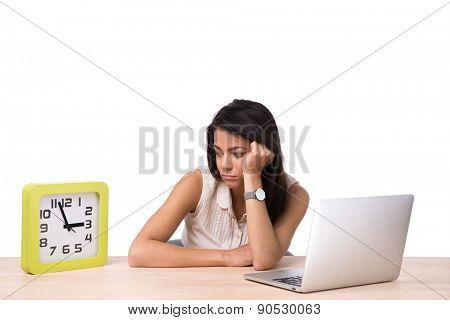 TIred businesswoman sitting at the table wth laptop and looking on the clock