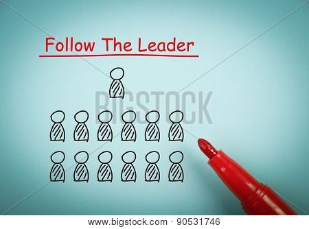 Follow the leader concept is on blue paper with a red marker aside. poster