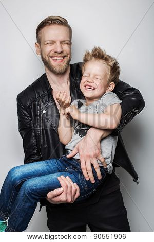 Young father and son laughing together. Fathers day