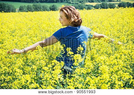 Young Woman Relaxing In Rapeseed Field