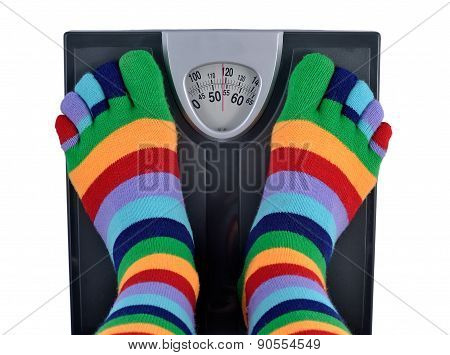 Feet in striped socks on a scale poster