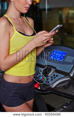 Fit girl in activewear listening to music in ipad in gym