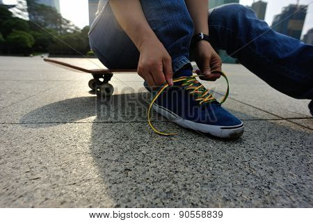 skateboarder tying shoelace at skate park