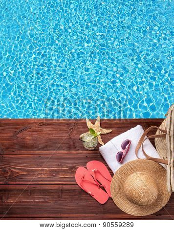 Swimming accessories on wooden mole placed next to water surface of pool. Shot from bird-eye perspective