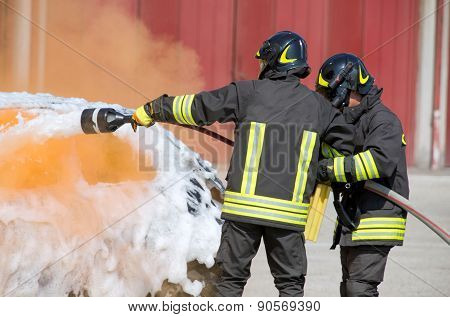 firefighters in action with foam to put out the fire of the car poster