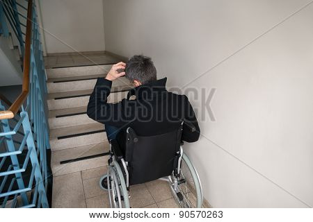 Rear View Of A Worried Disabled Man In Front Of Staircase poster