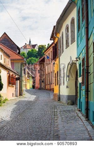 Stone Paved Old Street With Colored Houses From Sighisoara Fortresss, Transylvania