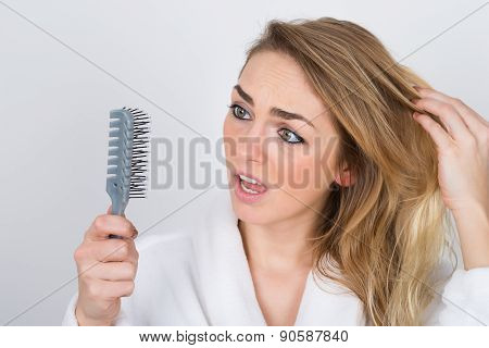 Worried Woman Looking At Comb