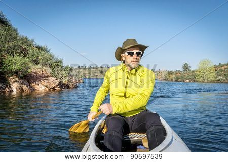 senior male paddling a decked expedition canoe on Horsetooth Reservoir, Fort Collins, Colorado, springtime scenery