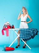 Full length sexy girl retro style ironing male shirt tired woman housewife in domestic role. Traditional sharing household chores. Pin up housework. Vivid blue background poster