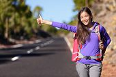 Travel hitchhiker woman backpacking hitchhiking thumbing happy walking on road side during holiday travel. Beautiful outdoors woman model. Mixed race Asian Caucasian poster