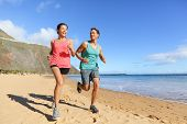 Runners running on beach. Jogging couple training on beach in full body length living healthy active lifestyle. Asian runner woman and fit male fitness athlete on run. poster
