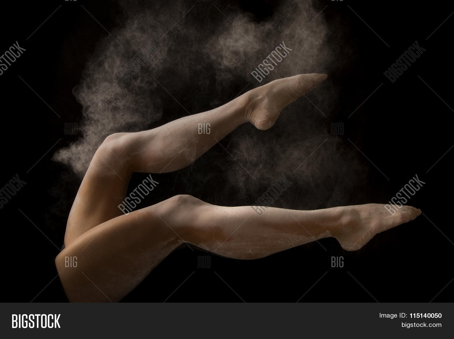 A woman's legs kicking and flexing with powder flying in the air.