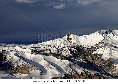 Winter Mountains At Sun Evening And Dark Clouds