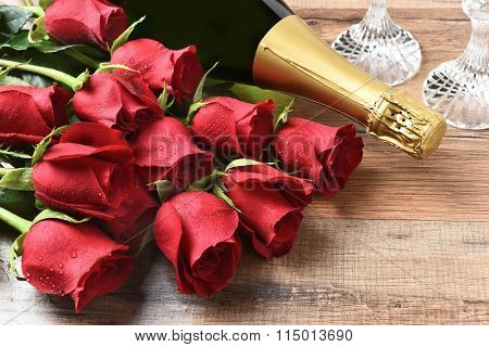 Closeup of a bottle of champagne and red roses on a wood table. Valentines Day / Love concept.