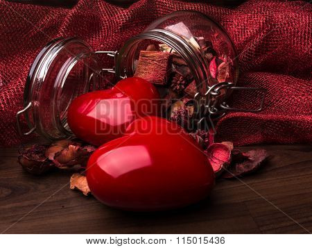 two hearts with jar of essences on wooden table