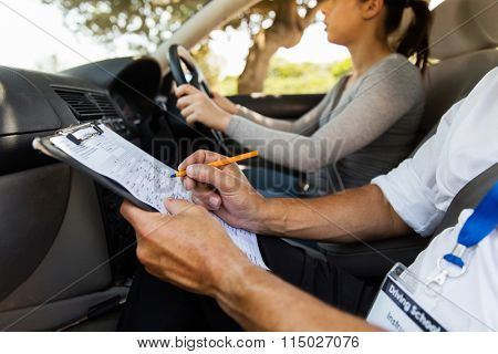 driving instructor inside a car with student driver doing checklist