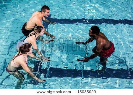 Fitness class doing aqua aerobics on exercise bikes in swimming pool