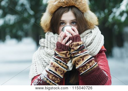 Portrait of girl with hiding her face behind tourist vacuum flask cup with hot drink outdoors