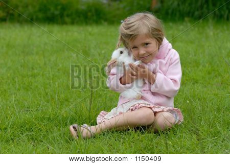 little girl with a rabbit sitting on the grass poster