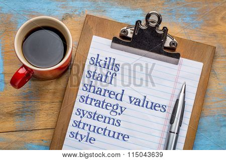 7S model for organizational culture, analysis and development (skills, staff, strategy, systems, structure, style, shared values) - text on a clipboard with a cup of coffee