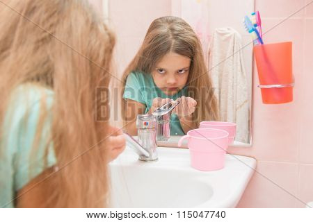 The Girl Washing Up Looked In The Mirror In The Bathroom