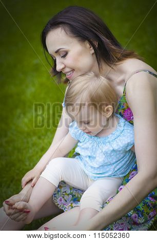 Beautiful Young Mother With Daughter Relaxing Sitting On Grass