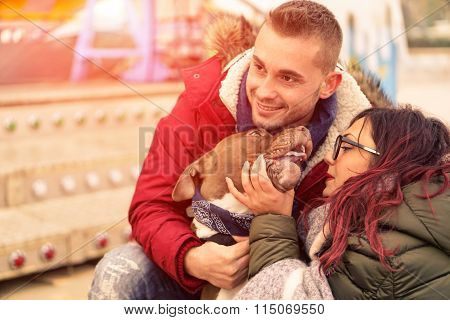 Young couple playing with dog next luna park carousel - Portrait of happy lovers with their pitbull