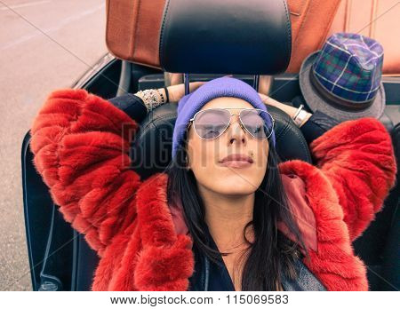Young hipster woman relaxing in cabrio auto after long trip