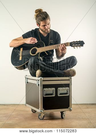 Handsome Man Sitting And Playing Guitar