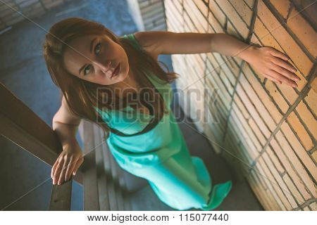 Young beautiful busty girl in the green dress with an open neckline andwith a mysterious look walks