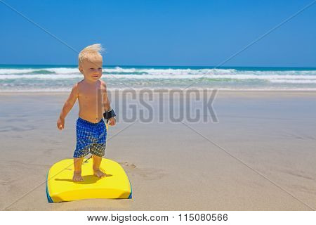 Little Child Swimming With Bodyboard On The Sea Sand Beach