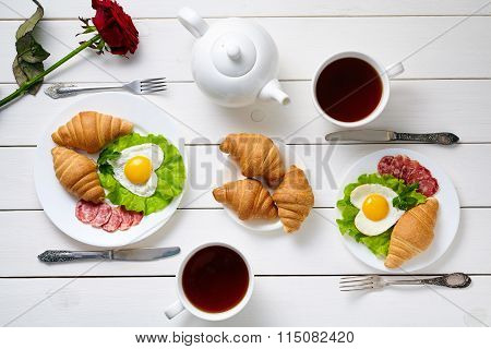 Romantic breakfast for two with heart shaped eggs, salad, croissants, rose flower and black tea on w